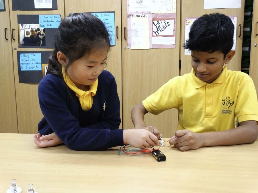 Primary children completing a science experiment