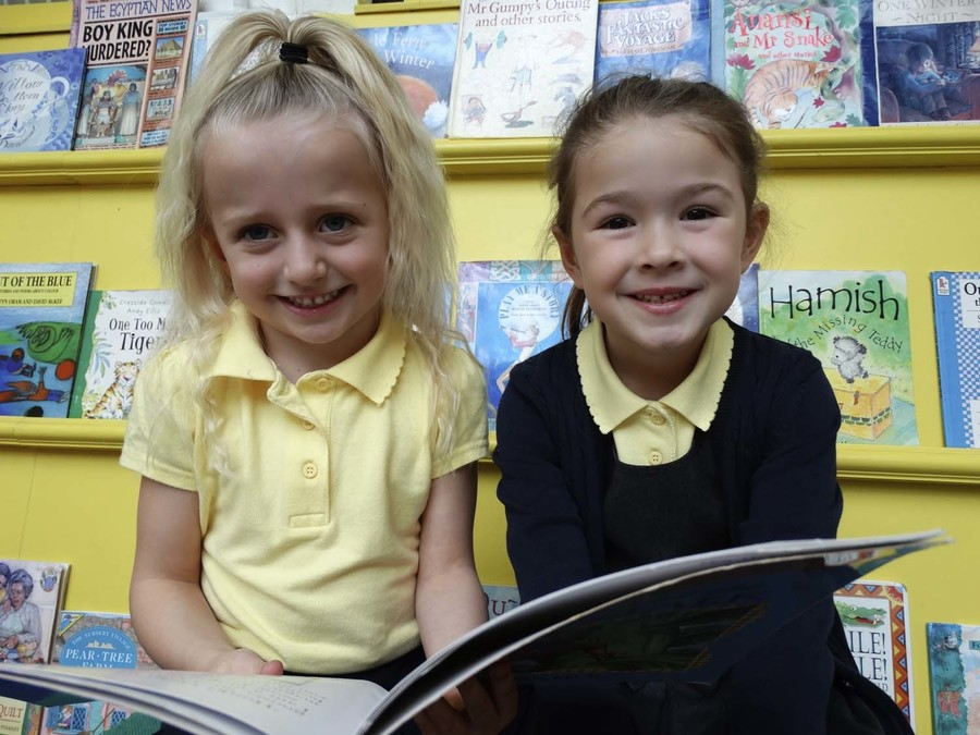 Two girls reading in school library