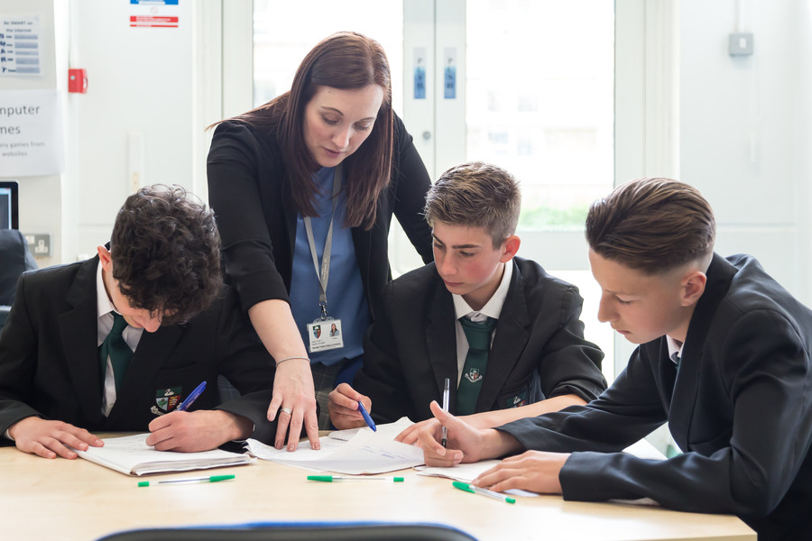 Students working in class with teacher